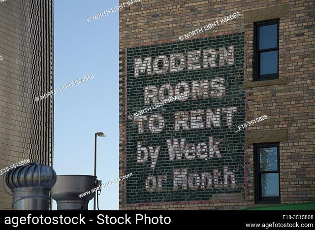 Canada, Alberta, Calgary. Old fashioned sign painted on the side of brick building, advertising rooms to rent