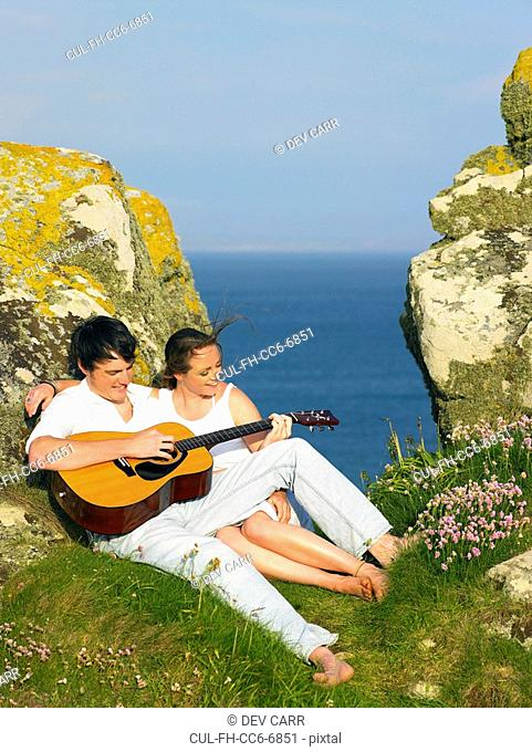 Young couple on a cliff playing guitar