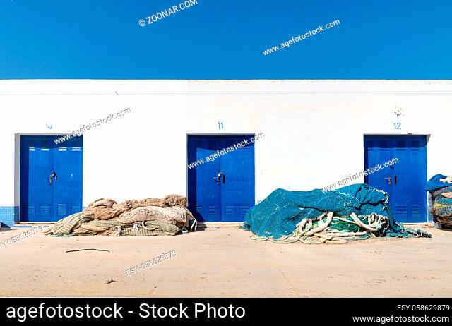 White harbour warehouse building with blue doors and fisher nets and cloudless blue sky, Altea, Costa Blanca, Spain