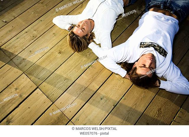 Couple Relaxing On Wood Deck
