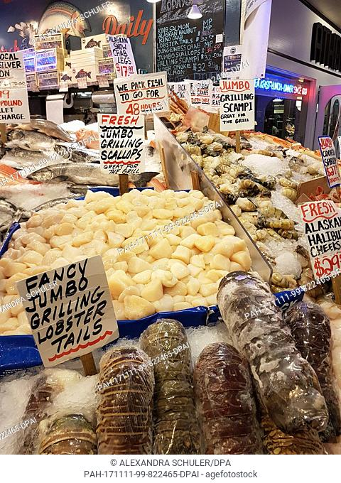 Fresh fish and crustaceans, scallop, lobster tails and scampi lie around for sale in a fish stand at the Pike Place Market in Seattle, United States