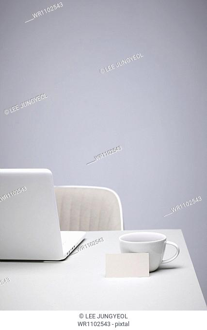 a coffee cup next to a laptop