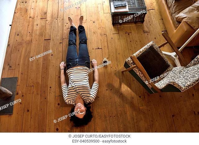 a woman lying on the floor of her house