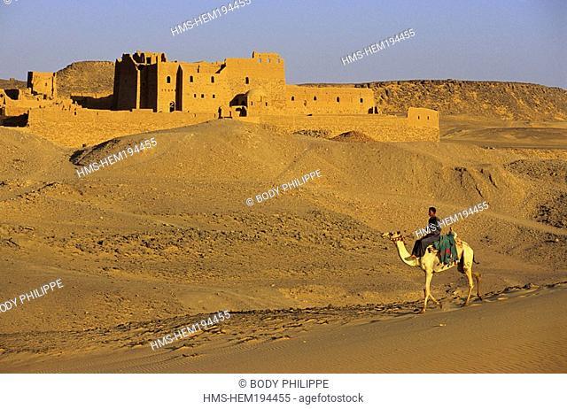 Egypt, Upper Egypt, Aswan, camel rider in the desert, Saint Simeon Monastery on the left bank of Nile River