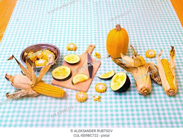 Still life of corn on the cob with two varieties of squash