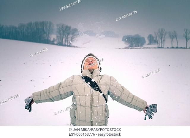Ecstatic middle aged woman enjoying snow in winter