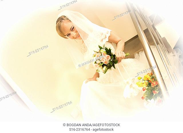 Happy winking young bride coming down a staircase adorned with roses