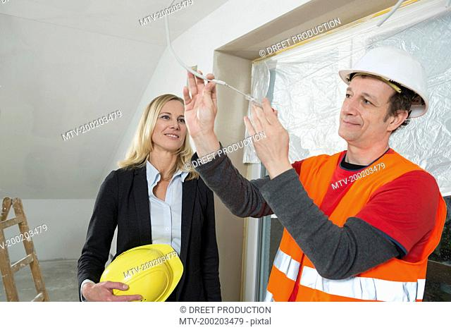 Female architect and construction worker at construction site of new building