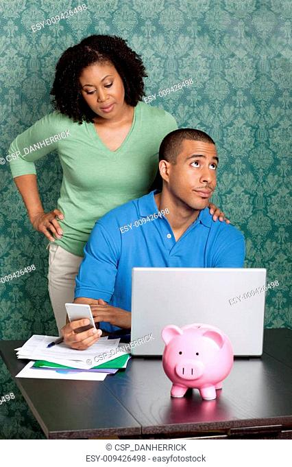 Young couple doing home accounts at home, using laptop