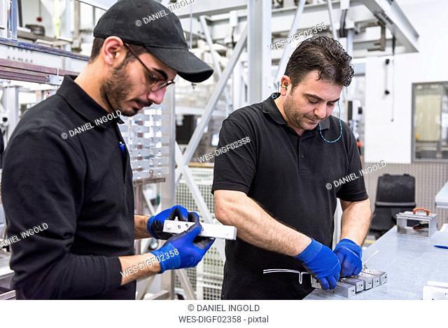 Two men working in factory shop floor