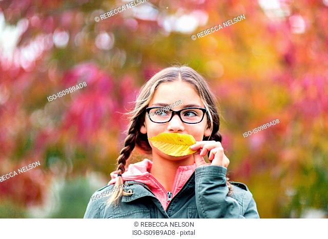 Portrait of girl with plaits and glasses covering mouth with leaf looking away