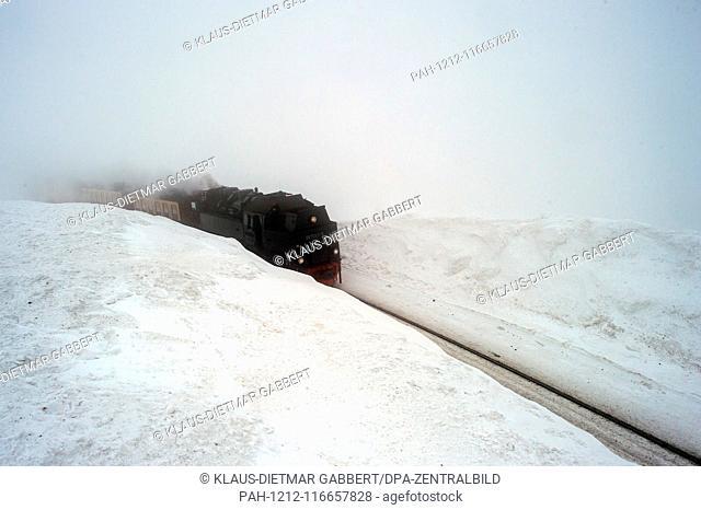 07 February 2019, Saxony-Anhalt, Brocken: The Brockenbahn of the Harzer Schmalspurbahnen (HSB) travels in the fog between two metres high snow drifts