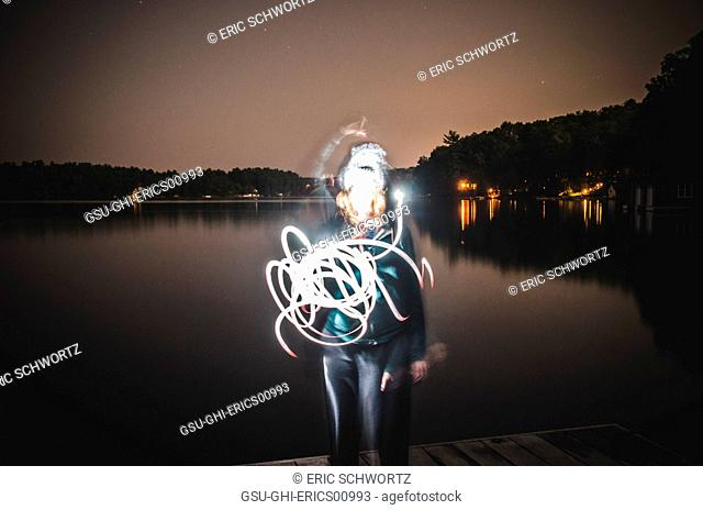 Young Woman Light Painting with Flashlight at Night on Dock