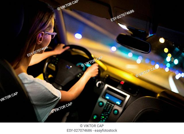Female drive driving a car at night (shallow DOF; colour toned image)