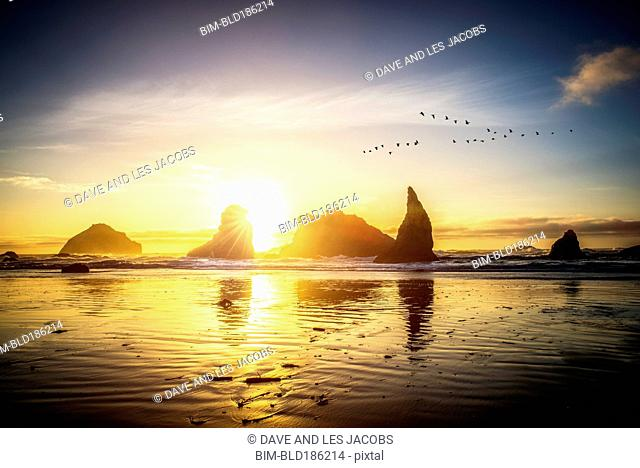 Silhouette of rock formations on sunny beach