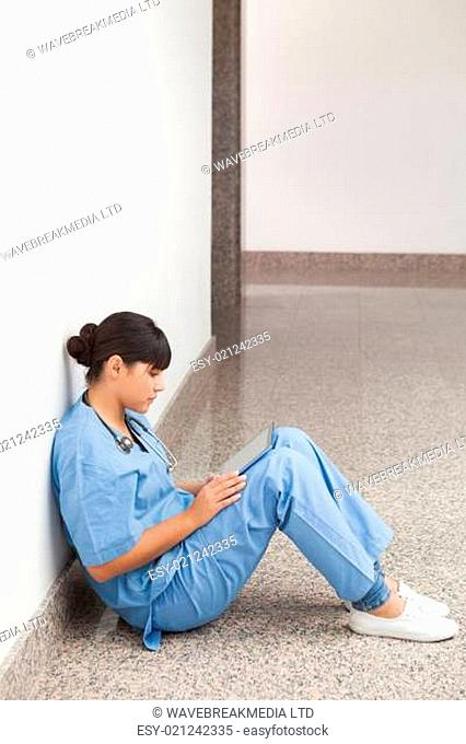 Nurse sitting on the ground looking at file in hospital corridor