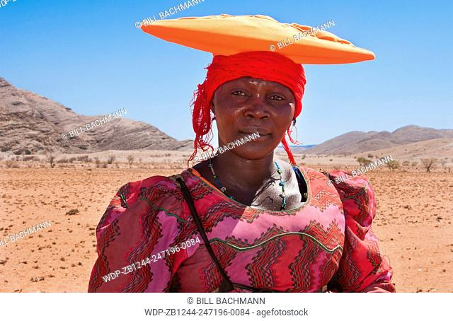 Namibia Africa Northern Desert Herero woman with hat riding mule herding goats in Tomakas in Puros Conservancy remote farming