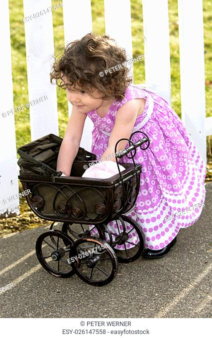 little girl playing with her pram in front of a white fence