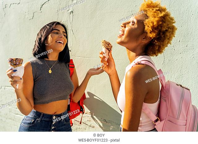 Two happy female friends with ice cream cones at a wall