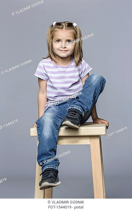 Cute smiling girl sitting on wooden stool against gray background