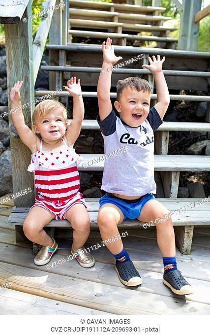 Two happy kids raise their hands in celebration, sitting on stairs