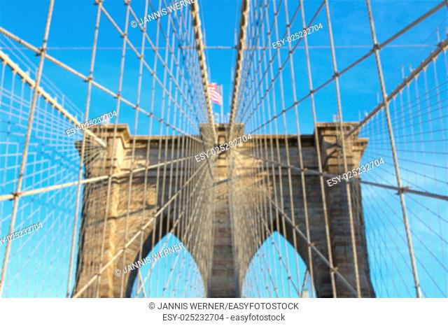 Blurred background of view up into at one of the towers holding up the Brooklyn Bridge in New York, NY, USA
