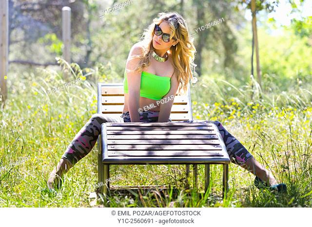 Attractive blonde young woman spread across wooden deckchair