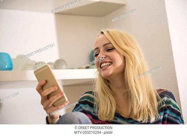 Beautiful young woman using smart phone in the living room and smiling, Bavaria, Germany