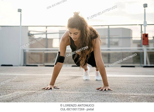 Young woman doing plank on rooftop deck