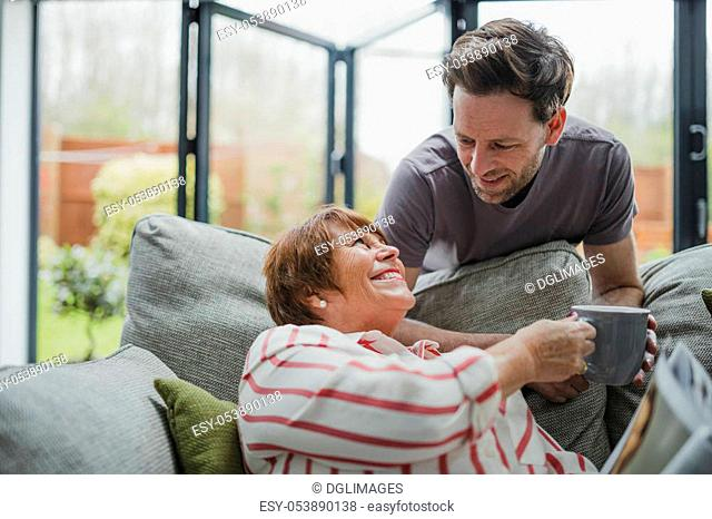 Man is leaning over the sofa to give his mother a cup of tea. She is sitting on the sofa and is taking it from him gratefully