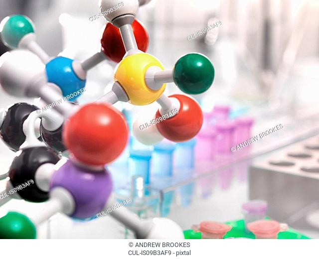 A molecular model of a chemical formula with laboratory equipment in the background