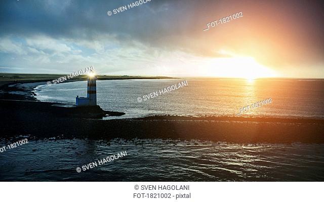 Idyllic sunset over ocean and old lighthouse, Reykjanesbaer, Iceland