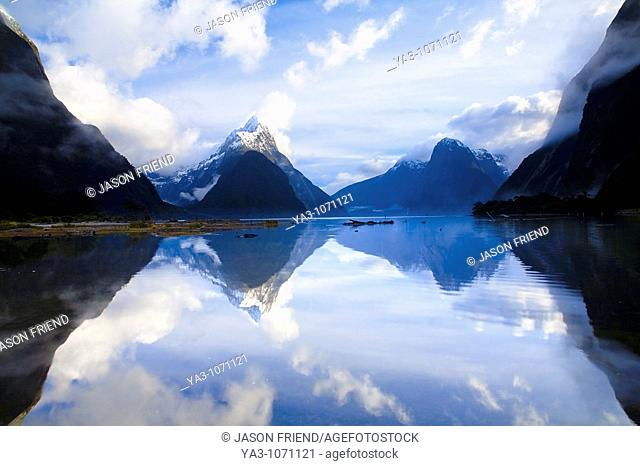 New Zealand, Southland, Fiordland National Park  A clearing storm above Mitre peak, reflected in the still waters of the Milford Sound