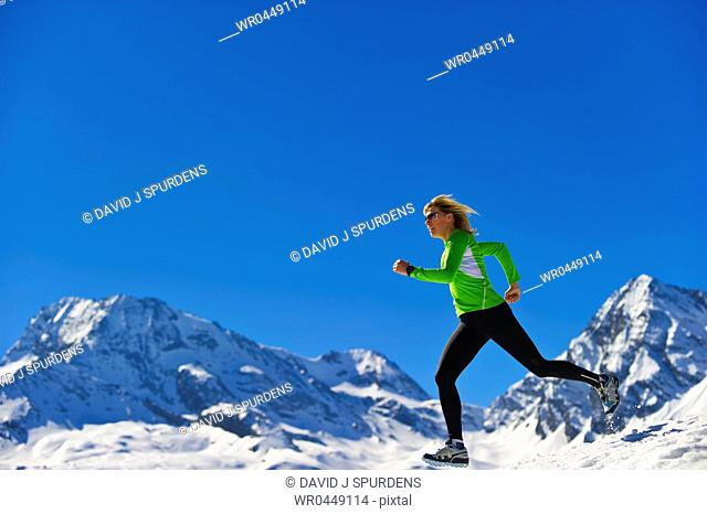 A woman jogging fast over snowy mountains
