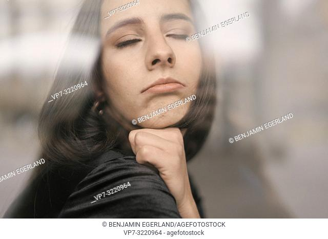 portrait of a woman curling lips, pout, closed eyes, defiant emotion, in Munich, Germany