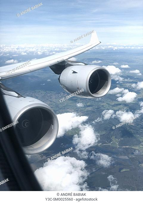 View from passenger airplane cabin after flight departure at wing and turbines above ground