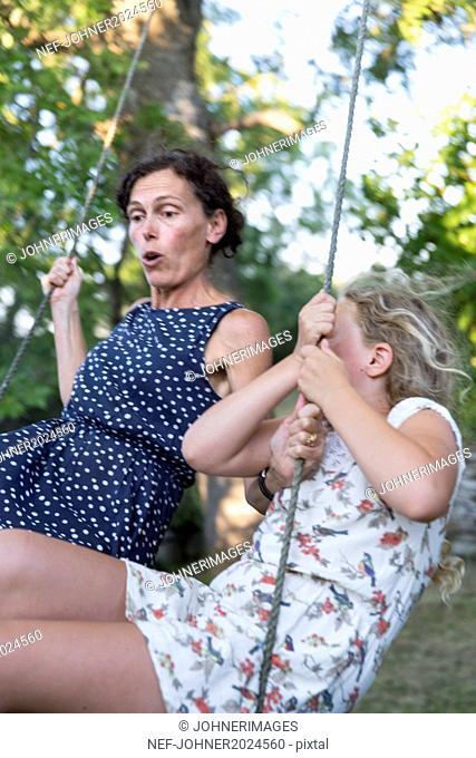 Mature woman with teenage daughter on swing