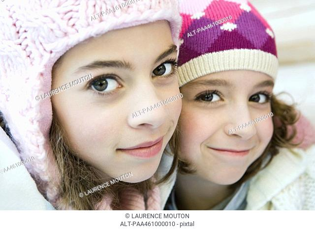 Two young sisters smiling at camera, both wearing knit hats, cheek to cheek, portrait