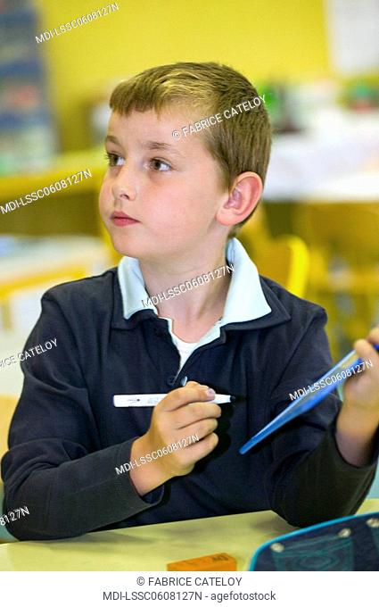 Young boy holding a plastic slate and a felt pen and looking sideways in a classroom