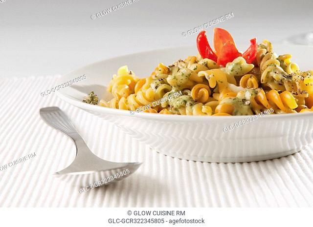 Close-up of a bowl of rotini topped with pesto sauce