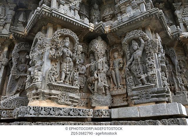 Ornate wall panel reliefs depicting (From left) Goddess Lakshmi, deities, a sage, and Krishna as Govardhan Giridhari, Kedareshwara temple, Halebidu, Karnataka
