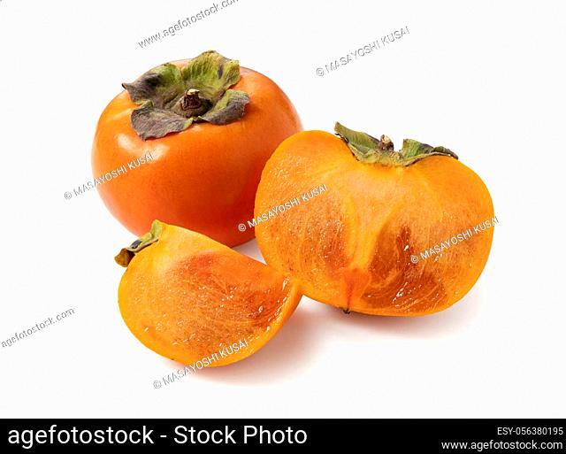 A cut Japanese persimmon placed on a white background. Focus stacking