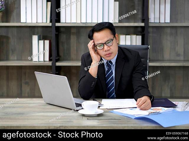 Sad Asian businessman touch his temple with one hand, sitting in the office. The concept of unemployed, sadness, depressed and human problems