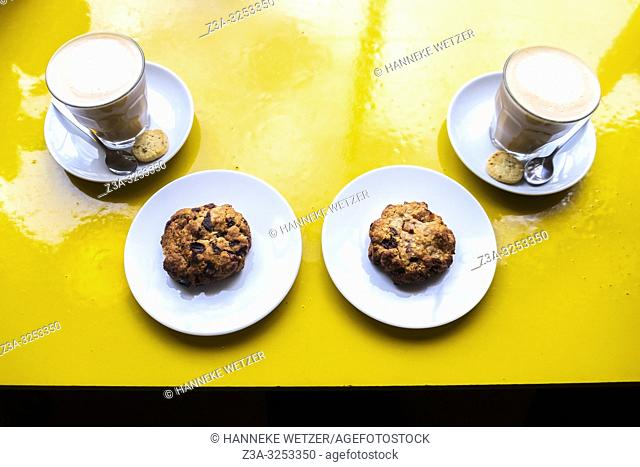 Coffee with oatmeal cookies on a yellow table