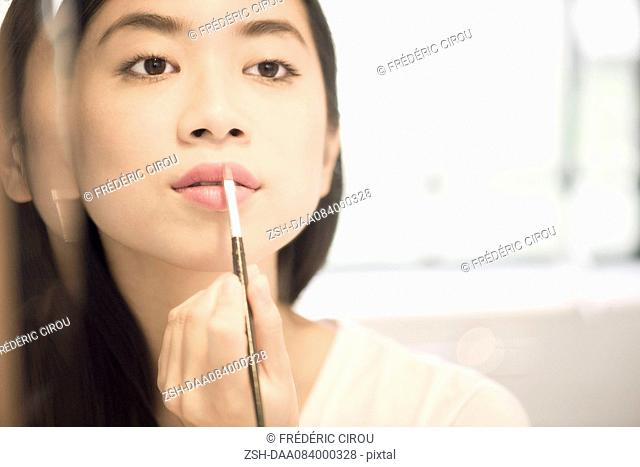 Woman using lipbrush to apply lipstick