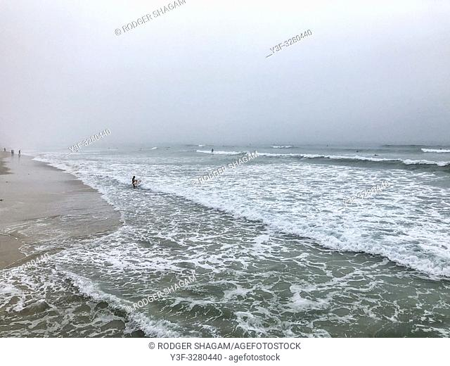 Mist-shrouded coastline as the tide recedes with a handfull of surfers in the distance. Cape Town, Soth Africa. Surfers can be seen in the far distance