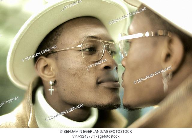 well-dressed man looking at himself in mirror, facing himself, self-perception, wearing Christian cross earring, faith, in Munich, Germany