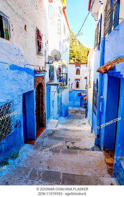 Narrow street painted blue in Chefchaouen city, Morocco