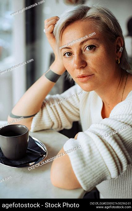 Blond woman sitting at table with cup of coffee looking at camera