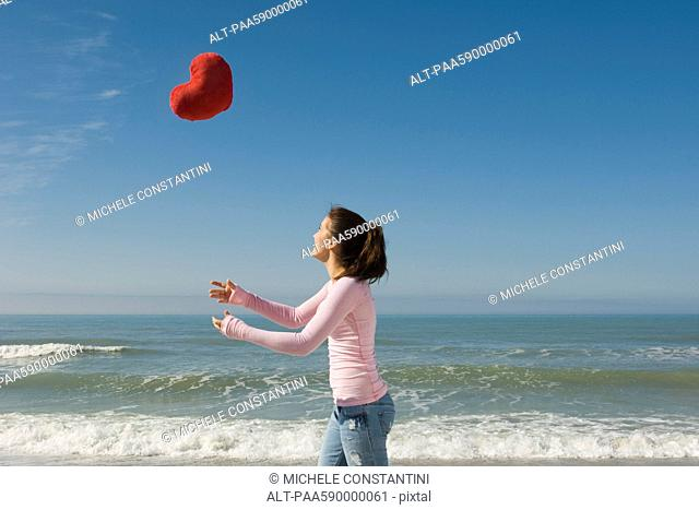 Preteen girl at beach tossing stuffed heart-shaped toy into air